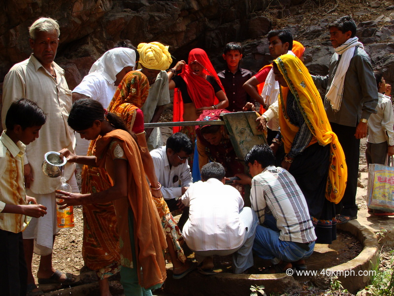 Crowd around a Hand Pump for Water